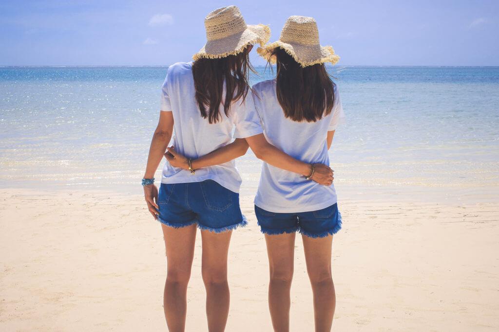 砂浜をバックにお互いの腰に手を回している女性