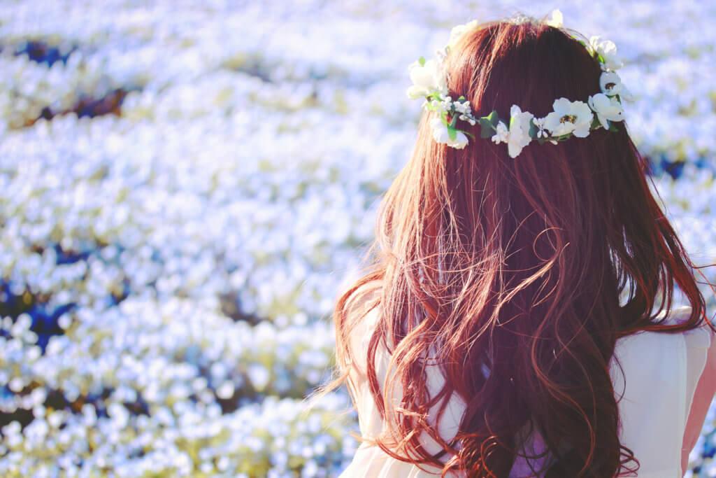 後ろを向いて花畑を見ている女性